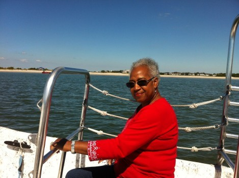 Woman on a boat off the coast with beach in the background